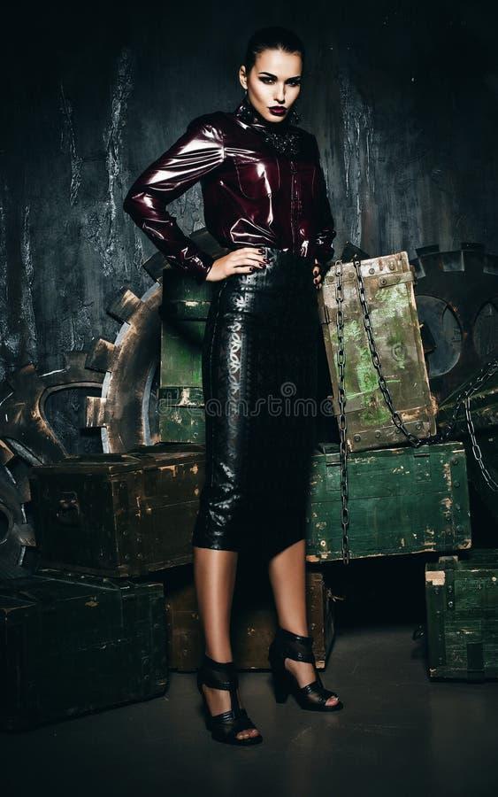 Mulher na saia de couro que está perto das caixas de madeira imagens de stock