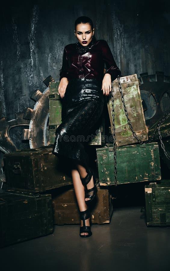 Mulher na saia preta que está perto das caixas de madeira foto de stock