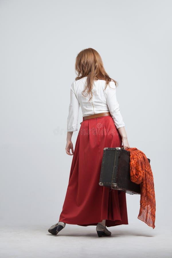 Mulher na saia vermelha do vintage com uma mala de viagem fotografia de stock royalty free