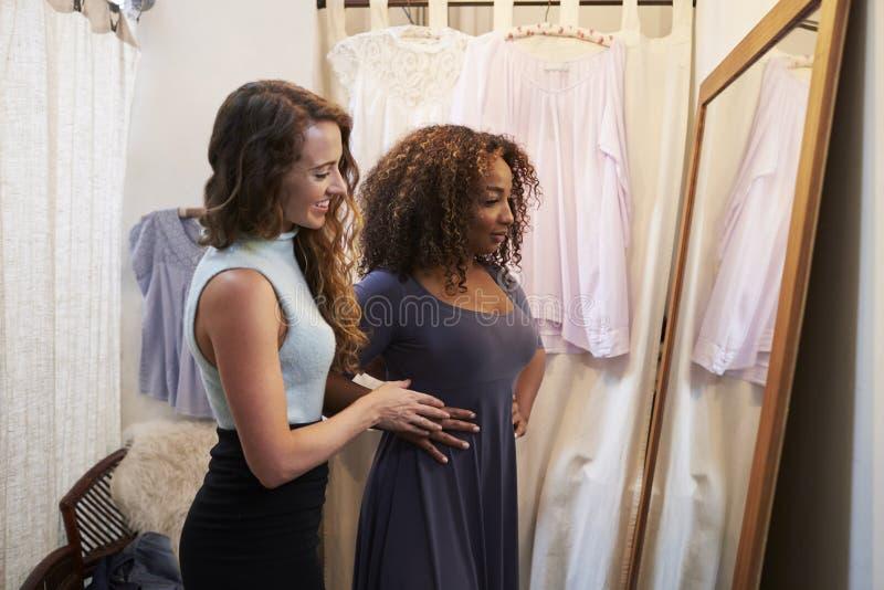 Mulher na sala de mudança do boutique com o amigo que tenta no vestido fotografia de stock