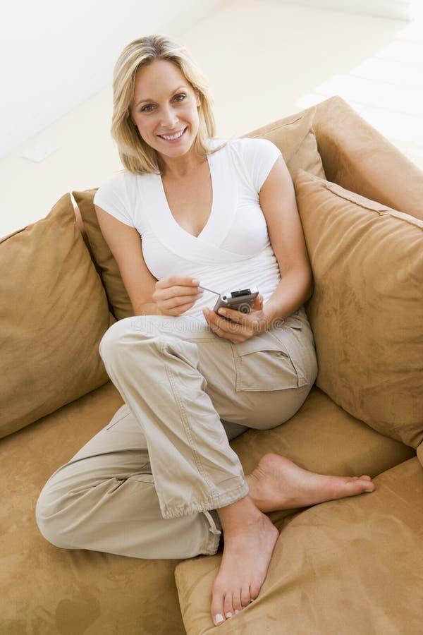 Mulher na sala de visitas usando PDA foto de stock royalty free