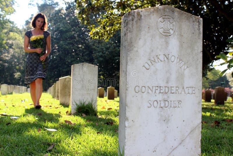Mulher na sepultura do ` s do soldado desconhecido com flores amarelas imagem de stock
