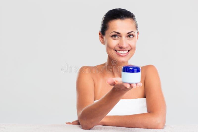 Mulher na toalha que senta-se na tabela e que guarda o frasco de creme imagem de stock royalty free