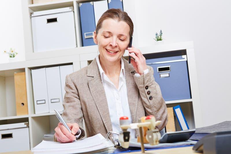 Mulher na utilização do escritório para negócios foto de stock