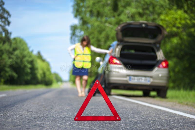 Mulher na veste reflexiva perto de carro quebrado imagem de stock