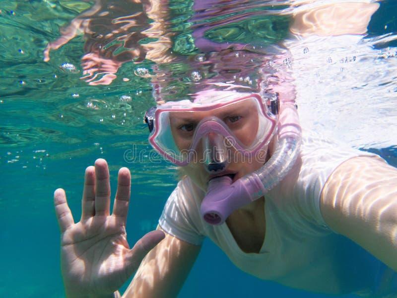 A mulher nada debaixo d'água com tubo de respiração fotografia de stock royalty free