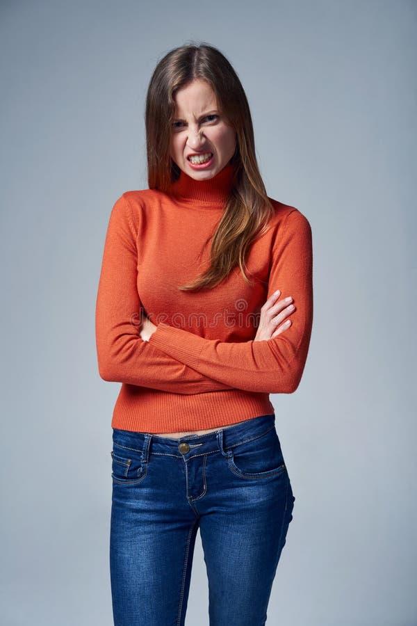 Mulher nas calças de brim com expressão facial irritada imagem de stock royalty free