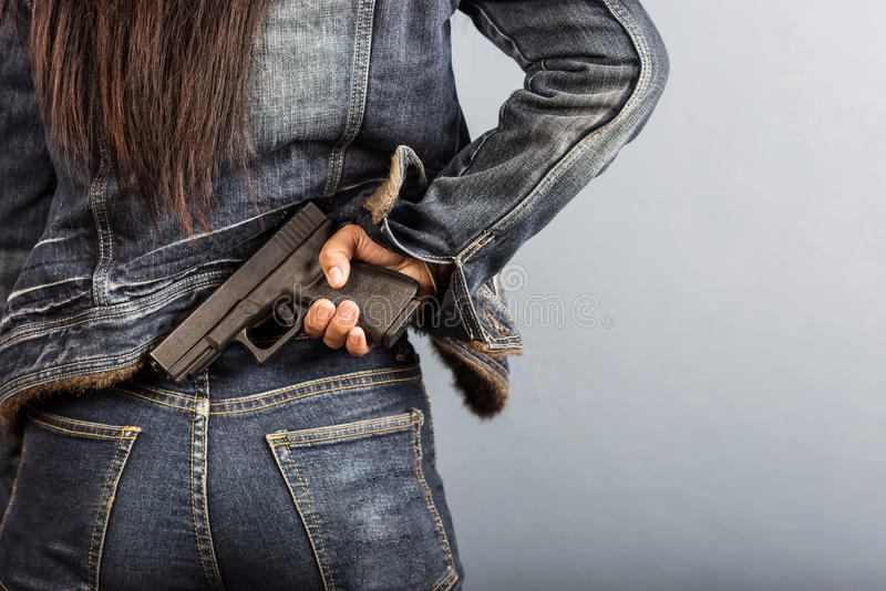 A mulher nas calças de brim está guardando uma arma fotografia de stock