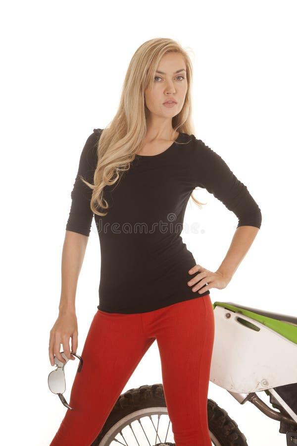 Mulher nas calças vermelhas que guardam vidros na frente da bicicleta fotografia de stock