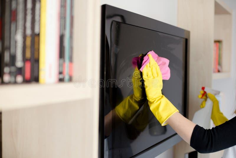 Mulher nas luvas de borracha amarelas que limpam a tevê fotos de stock royalty free