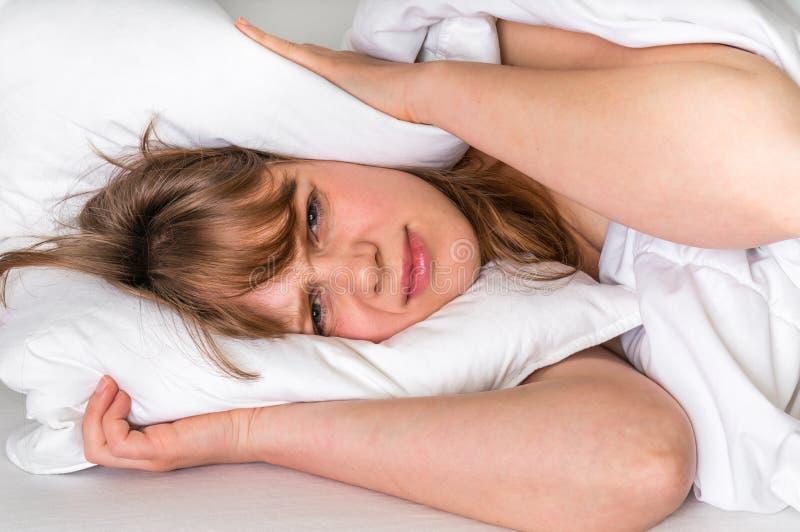 Mulher nas orelhas da coberta de cama com o descanso devido ao ruído fotografia de stock royalty free