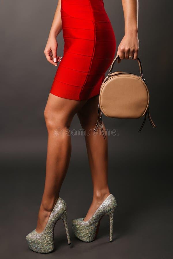 Mulher nas sapatas cravadas vermelhas do vestido curto vermelho que guardam a bolsa, pés fêmeas nos saltos altos fotografia de stock