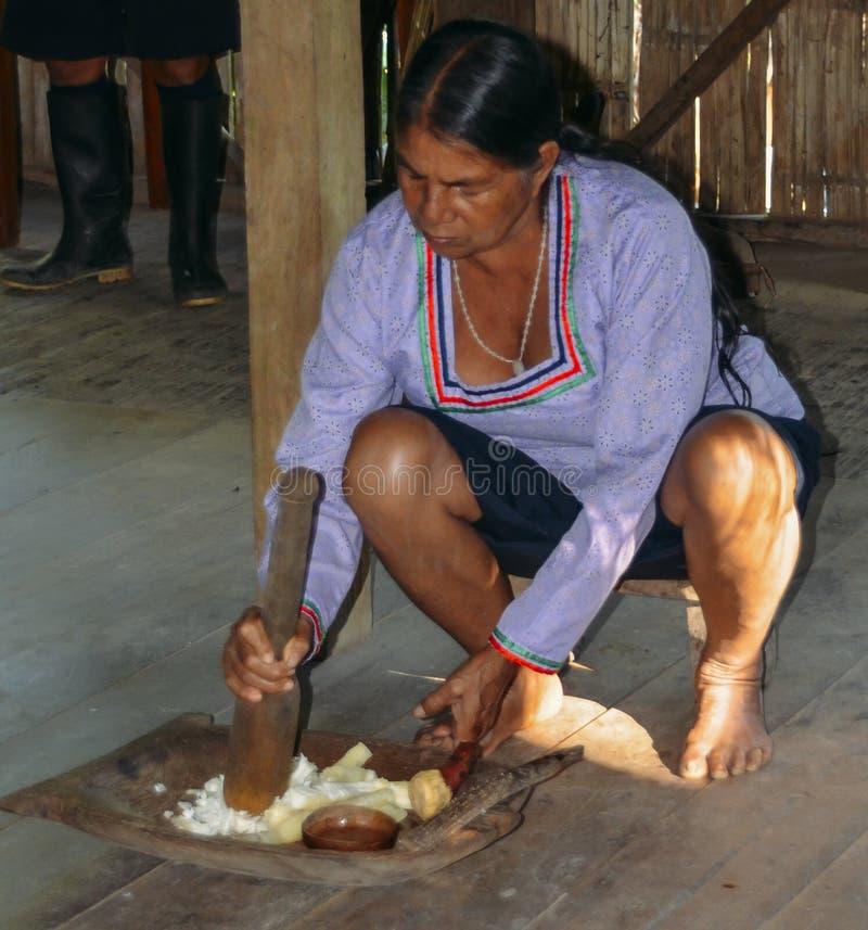A mulher nativa equatoriano Quechua local esmaga um tipo da mandioca, mandioca, em um método tradicional imagens de stock royalty free