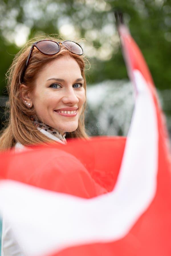 Mulher natural nova com a bandeira da terra arrendada do sorriso de Áustria no parque fotos de stock