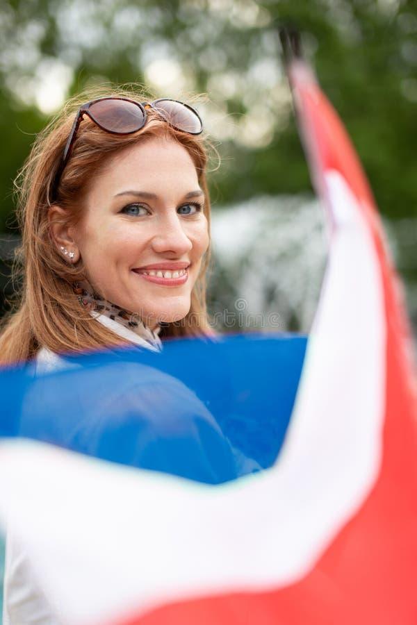 Mulher natural nova feliz com a bandeira da terra arrendada do sorriso de Países Baixos no parque imagens de stock