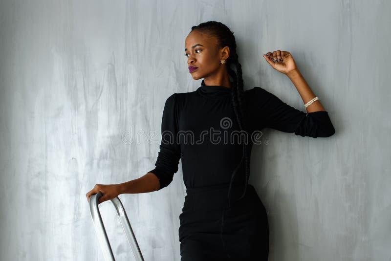 Mulher negra bonita e 'sexy' no vestido escuro que levanta olhando a mão afastado de inclinação na parede cinzenta no estúdio fotografia de stock