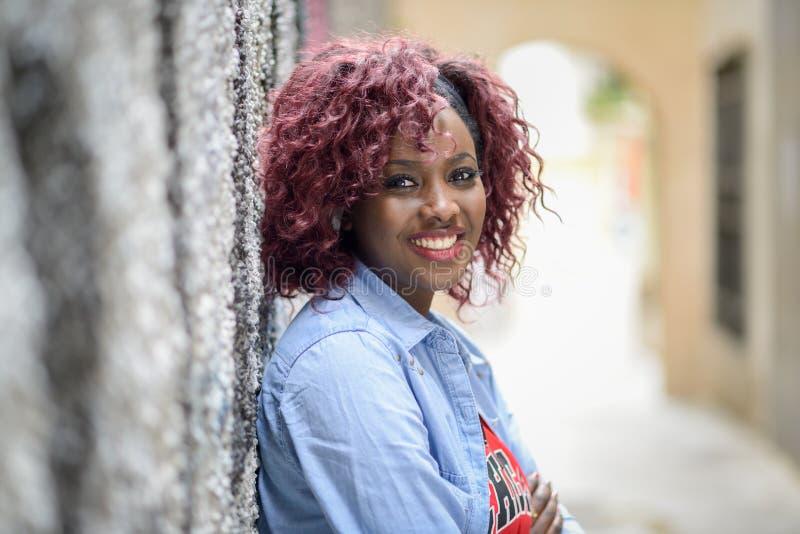Mulher negra bonita no fundo urbano com cabelo vermelho imagens de stock royalty free