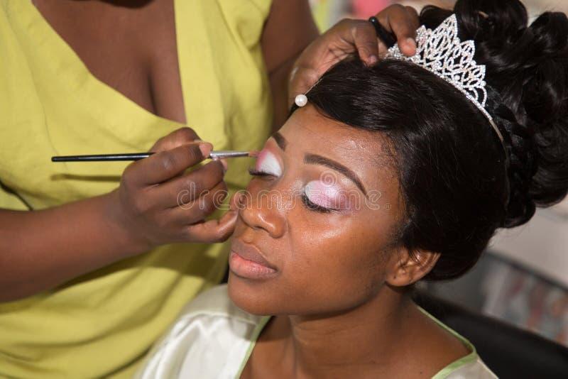 A mulher negra bonita nova do americano que obtém seus olhos compõe feito pelo artista profissional que usa a escova que aplica a fotos de stock