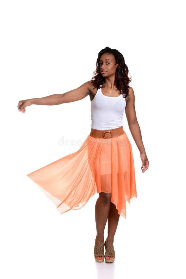 Mulher negra brincalhão com saia alaranjada foto de stock