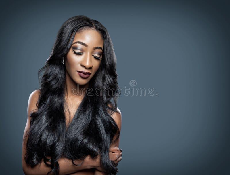 Mulher negra com cabelo brilhante luxuoso longo imagem de stock royalty free