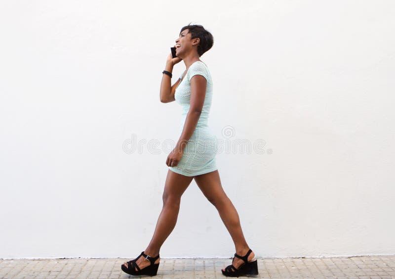Mulher negra de sorriso que anda na rua com telefone celular imagens de stock royalty free