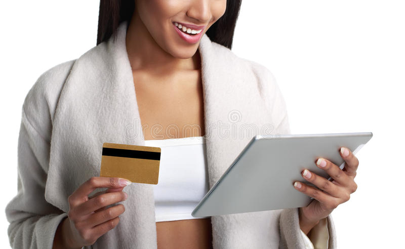 Mulher negra do mulato que guarda o tablet pc digital e o pagamento do cartão de crédito do ouro Opinião do Close-up No branco foto de stock