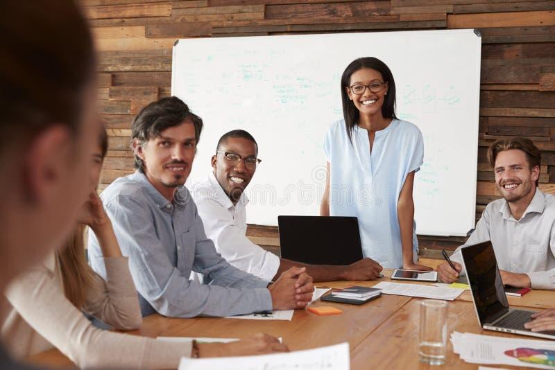 A mulher negra e os colegas novos na reunião sorriem à câmera imagem de stock