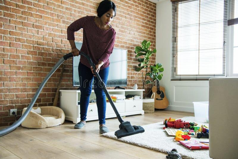A mulher negra está limpando a sala de visitas fotografia de stock