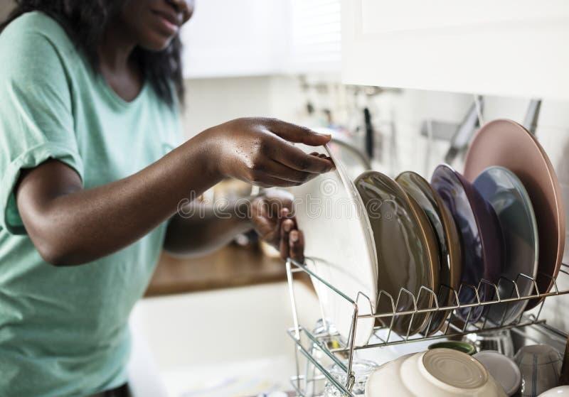 A mulher negra lavou os pratos fotografia de stock royalty free