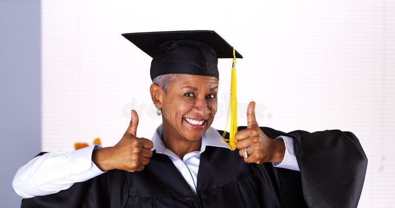 Mulher negra madura entusiástica no vestido da graduação foto de stock royalty free
