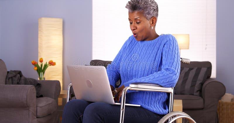 Mulher negra madura que senta-se na cadeira de rodas com portátil fotos de stock royalty free