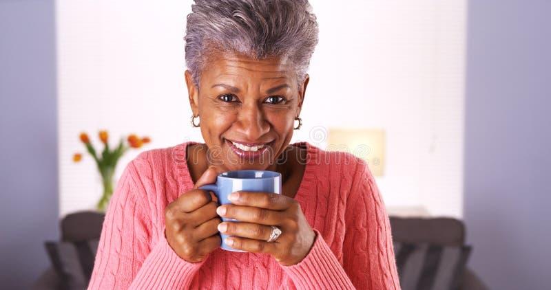 Mulher negra madura que sorri com caneca de café fotografia de stock