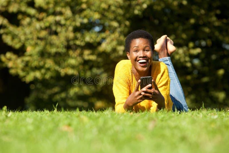 Mulher negra nova alegre que encontra-se no parque com telefone celular fotografia de stock royalty free