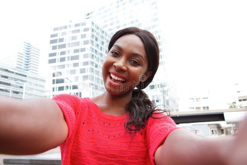 Mulher negra nova alegre que toma o selfie na cidade fotos de stock royalty free