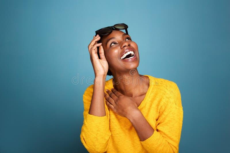 Mulher negra nova bonita nos óculos de sol que ri pela parede azul imagens de stock