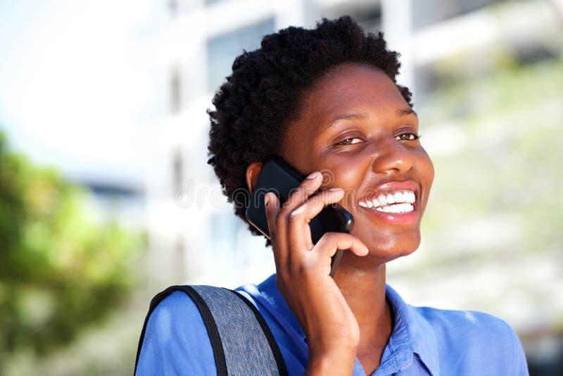Mulher negra nova bonita que fala no telefone esperto fora e no sorriso fotografia de stock