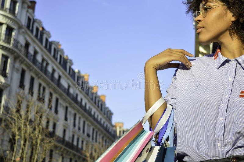 Mulher negra nova bonita que guarda sacos de compras Conceito sobre a compra, o estilo de vida e os povos imagens de stock
