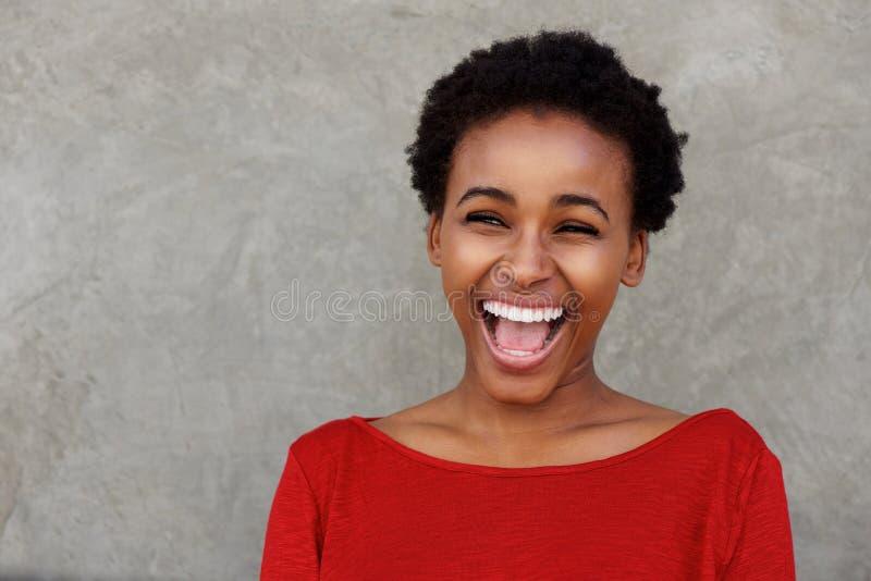 Mulher negra nova bonita que ri com boca aberta fotografia de stock royalty free