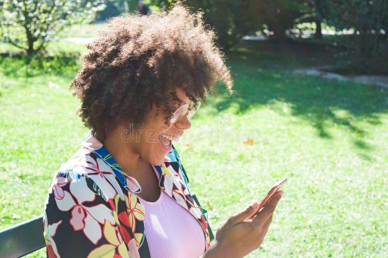 Mulher negra nova bonita que ri e que olha o smartphone no parque imagens de stock royalty free
