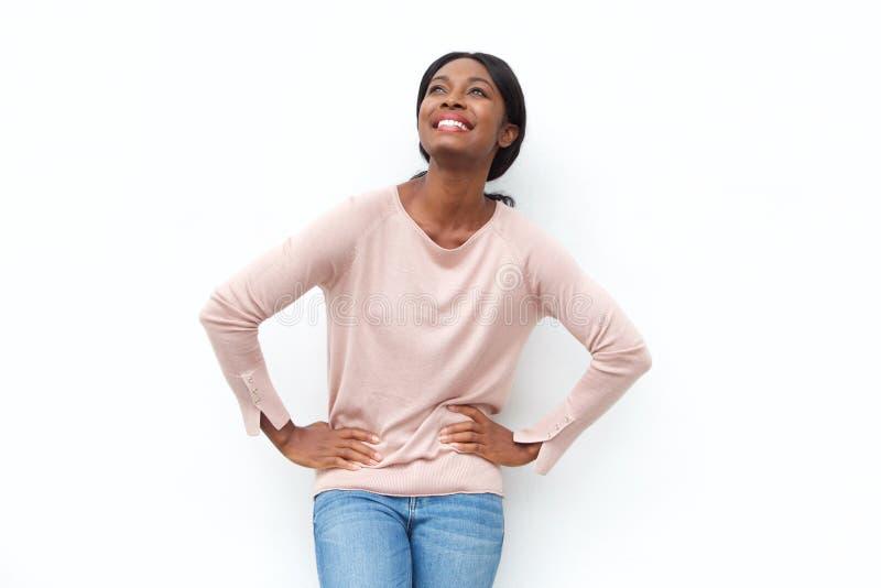 Mulher negra nova bonita que sorri com mãos nos quadris e que olha acima fotografia de stock