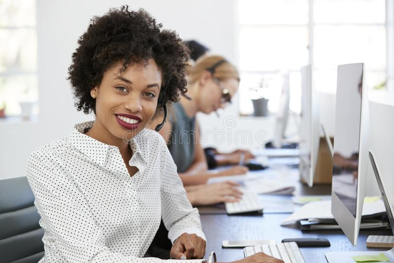 Mulher negra nova com auriculares que sorri à câmera no escritório imagem de stock royalty free