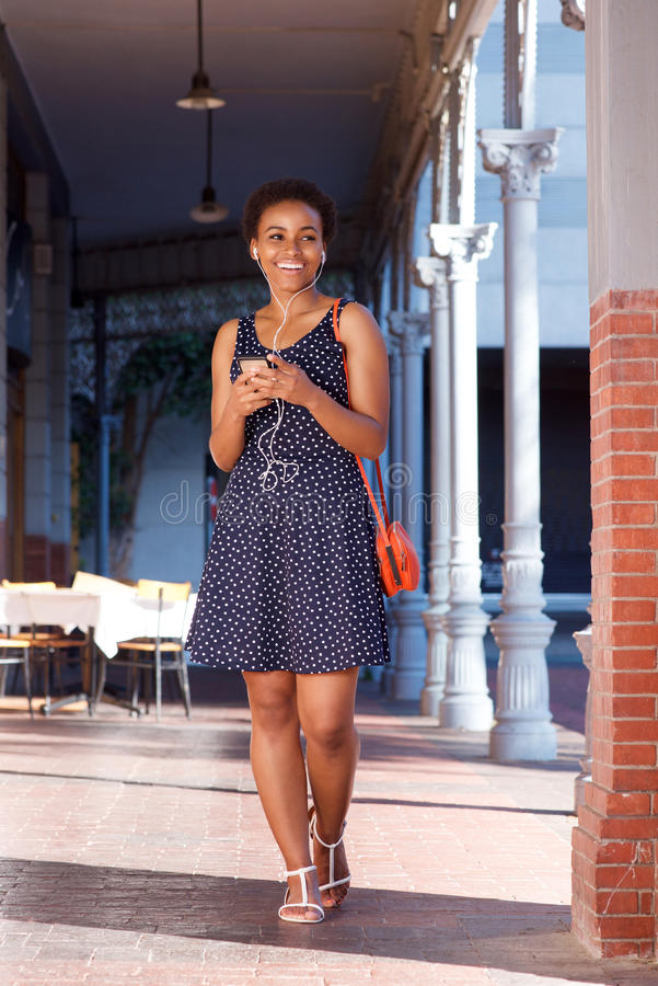 Mulher negra nova de sorriso que anda com telefone celular e fones de ouvido fotografia de stock