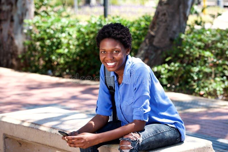 Mulher negra nova de sorriso que senta-se fora com um telefone celular fotos de stock royalty free