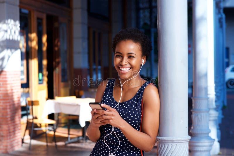 Mulher negra nova feliz que escuta a música com telefone e os fones de ouvido espertos fotografia de stock royalty free