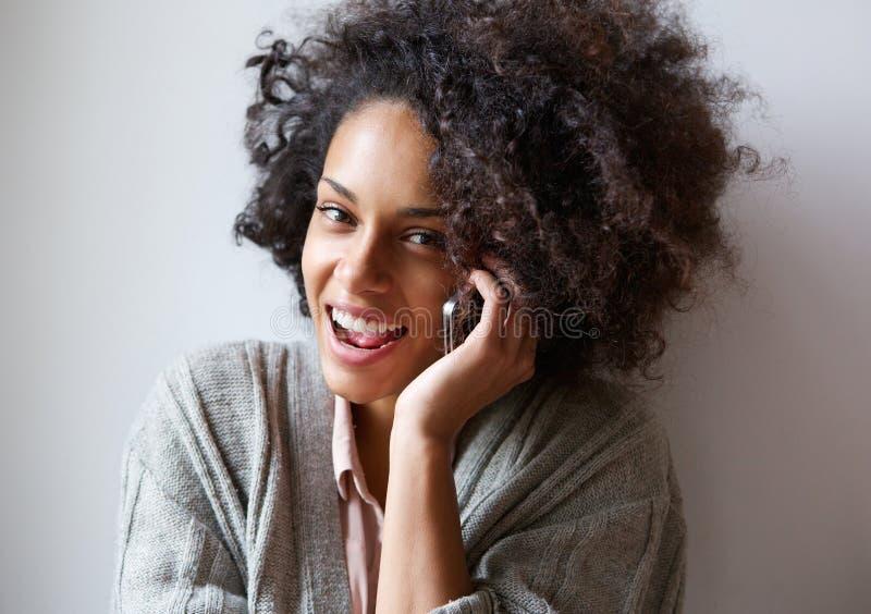 Mulher negra nova feliz que fala no telefone celular imagem de stock royalty free