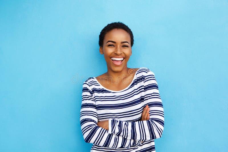 Mulher negra nova feliz que ri contra a parede azul imagem de stock royalty free