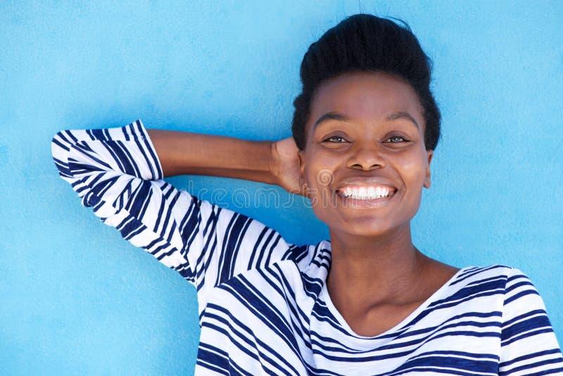Mulher negra nova feliz que sorri com mão atrás da cabeça imagens de stock royalty free