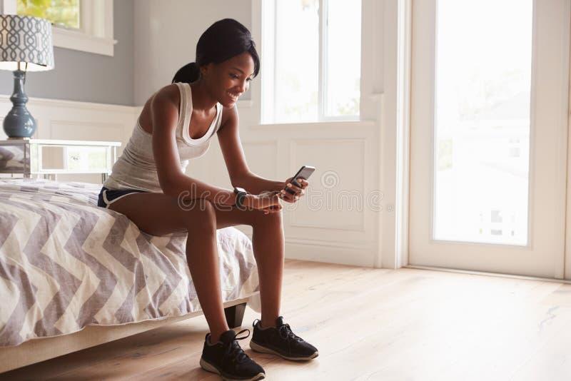Mulher negra nova pronta para o exercício, verificando o smartphone imagem de stock