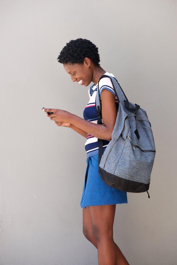 Mulher negra nova que anda e que usa o telefone celular no fundo cinzento fotografia de stock