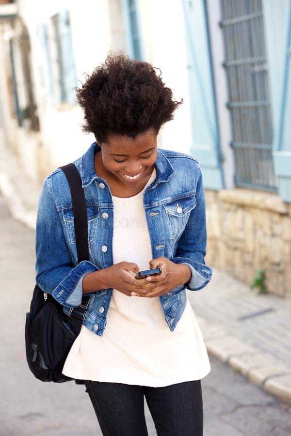 Mulher negra nova que anda fora com telefone celular fotos de stock royalty free